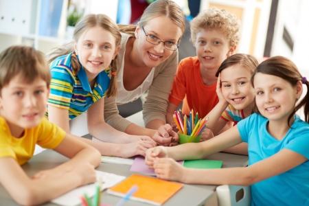 insegnante: Ritratto di scolari diligenti e insegnante guardando la fotocamera a lezione