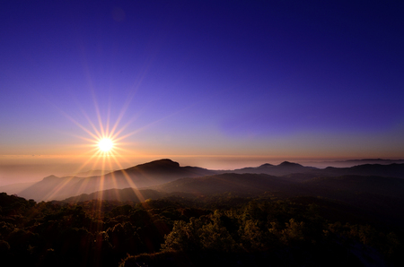 A power of sunrise above a mountain peak looks warm in a calm morning Stock Photo - 28189511