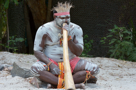 Portrait of one Yugambeh Aboriginal man play Aboriginal  music on didgeridoo, instrument during Aboriginal culture show in Queensland, Australia. Stock Photo - 46958198
