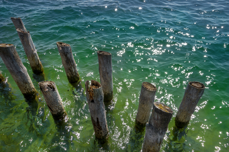 poles water: Old wooden posts in the water Stock Photo