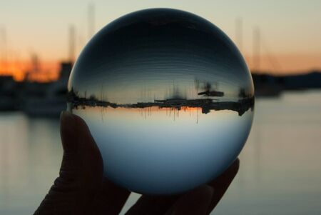 clear crystal ball: Crystal ball in hand with boats and sunset reflected