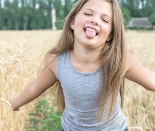 Playful Little Girl Showing Her Tongue In Wheat Field At A Summer Day