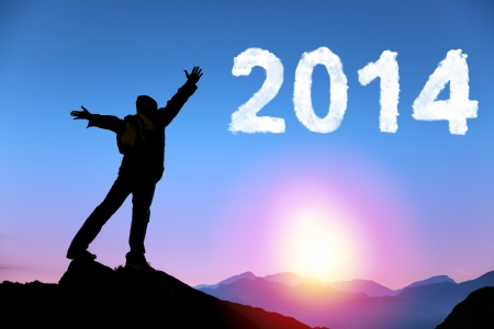 happy new year 2014.happy young man standing on the top of mountain Stock Photo - 24097354