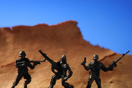 War metaphor, toy little soldiers fighting on wooden mountain Stock Photo - 4986656