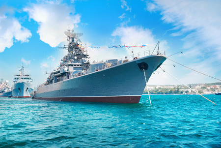 navy ships: Military navy ship in the bay. Military sea landscape with blue sky and clouds Stock Photo