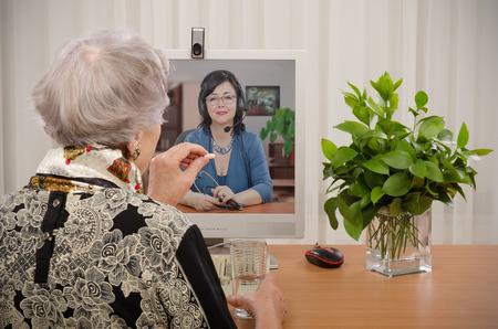 Mujer mayor que toma una píldora delante del médico virtual en la pantalla del monitor Foto de archivo - 40853798
