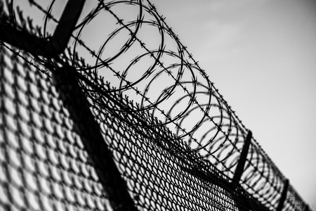 Prison Fence in Black and White. Barbed Wire Fence Closeup. Stock Photo - 37860362