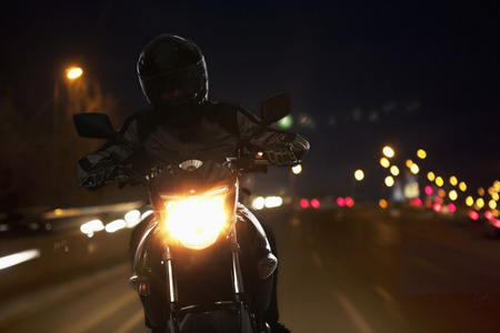 motorcycle crash: Young Man riding a motorcycle at night through the streets of Beijing Stock Photo