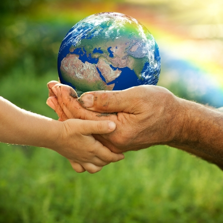 Hands of senior man and baby holding Earth against a rainbow in spring  Ecology concept Stock Photo - 12580809