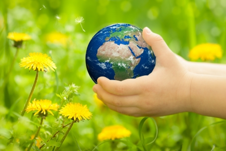 Planet Earth in children s hands against spring flowers  Elements of this image furnished by NASA Stock Photo - 17642632