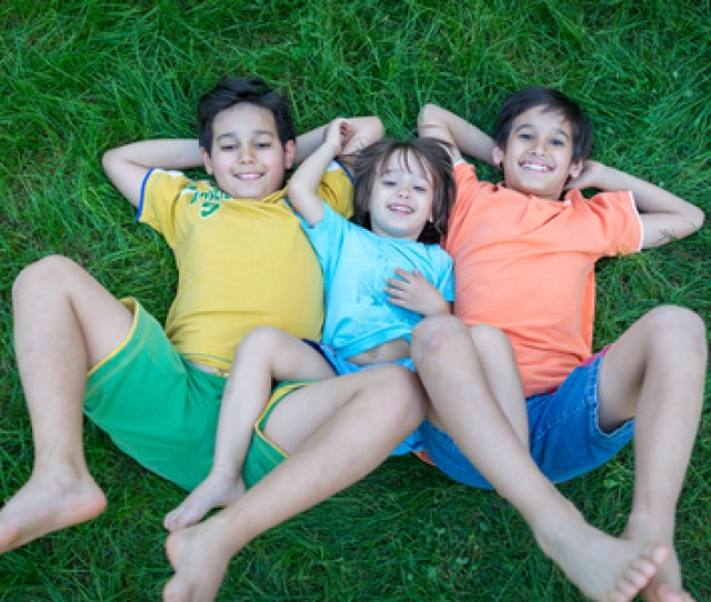 Group Of Cute Happy Children In Summer Lying On Green Grass With Feet Up Stock Photo