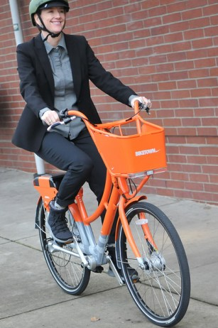 Portland's transportation chief Leah Treat shows off one of the new Biketown bikes, from sponsor Nike. Photo: Bike Portland
