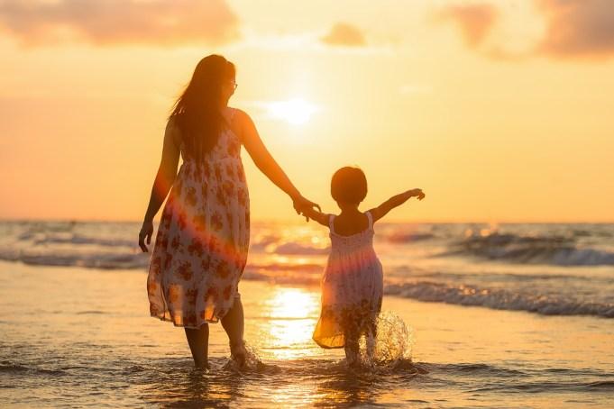 夕日の海で遊ぶ女性と子どもの親子