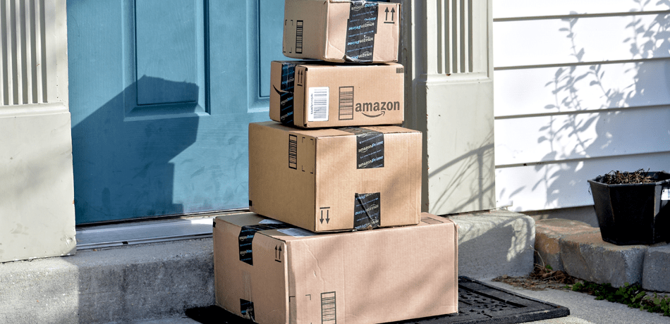 Amazon packages are piled up in front of a door.
