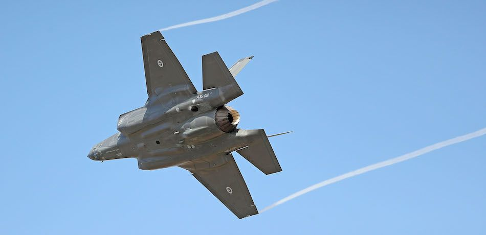 An F-35 flies against a blue sky.