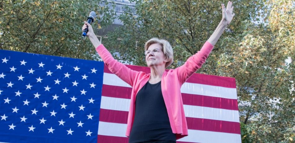 Sen. Elizabeth Warren waves as she takes the stage during a Town Hall at Keene State College.