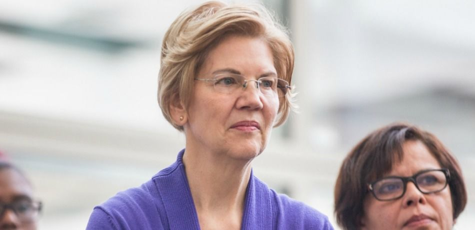 Sen. Elizabeth Warren listens during a rally for airport workers affected by the government shutdown at Boston Logan International Airport.