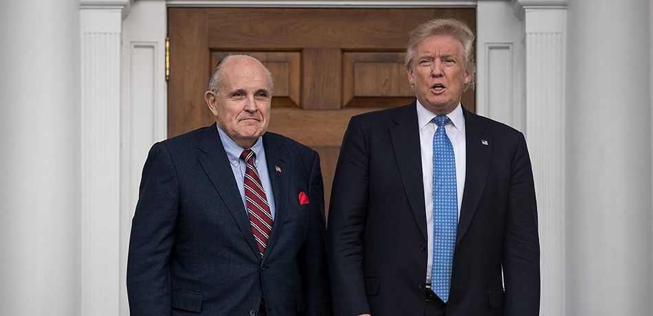 Former New York City mayor Rudy Giuliani stands with president-elect Donald Trump before their meeting at Trump International Golf Club, November 20, 2016 in Bedminster Township, New Jersey.