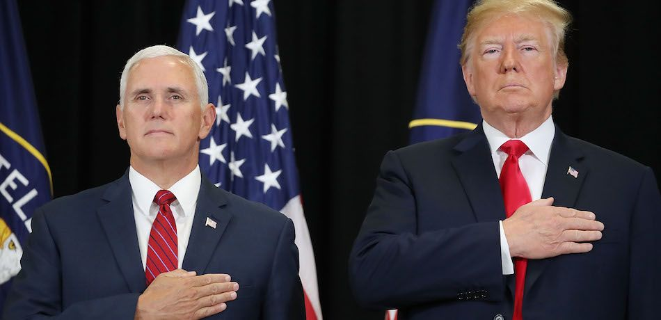 Mike Pence and Donald Trump pledge allegiance to the flag.