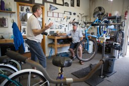 Kevin Hand (r) shares the story of how he found his way to Apalachicola, FL to start up his bike shop, Apalachicola Community Bikes, with Tom. / ©2017 Audrey Horn / www.usathroughoureyes.com