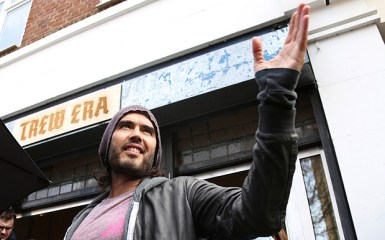 Russell Brand speaks at the opening of The Trew Era Cafe, a social enterprise community project on the New Era estate in east London, Thursday, 26 March, 2015. The opening of the cafe coincides with the trade paperback publication date of 'Revolution', and Brand will be donating 100% of his money for the book to the Cafe.(Photo by Joel Ryan/Invision/AP)