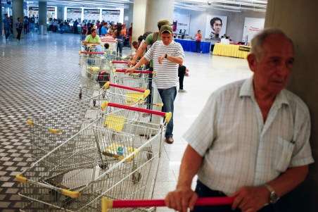 "Customers line up to get in for shopping at a state-run Bi centenario supermarket in Caracas May 2, 2014.  President Nicolas Maduro is introducing a controversial shopping card intended to combat Venezuela's food shortages but decried by critics as a Cuban-style policy illustrating the failure of his socialist policies. Maduro, the 51-year-old successor to Hugo Chavez, trumpets the new ""Secure Food Supply"" card, which will set limits on purchases, as a way to stop unscrupulous shoppers stocking up on subsidized groceries and reselling them. REUTERS/Jorge Silva (VENEZUELA - Tags: POLITICS BUSINESS SOCIETY TPX IMAGES OF THE DAY) - RTR3NL83"