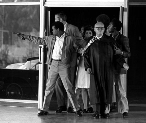 - - Group leaves the the Civic Center with a shotgun taped around Judge Harold Haley's neck. The inmate at left, James McClain, was fatally wounded in the van as it attempted escape. (IJ photo/Roger Bockrath)