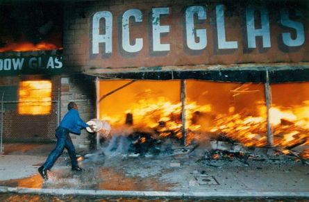 Cornelius Pettus, owner of Payless market, throws a bucket of water on the flames at next-door business Ace Glass on 4/30/1992. Hyungwon Kang / Los Angeles Times.