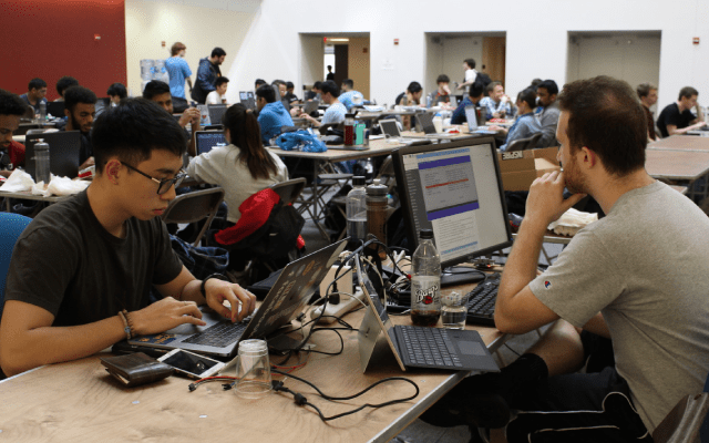 Students working on laptops at a hackathon.