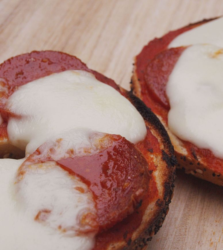 A pizza bagel with sauce, mozzarella cheese, and pepperoni sausage.