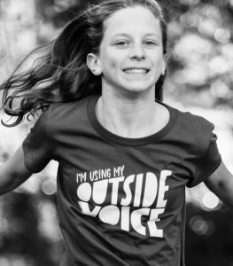 """Black and white image of a blonde haired girl wearing a t-shirt with a logo that says, """"I'm using my outside voice"""""""