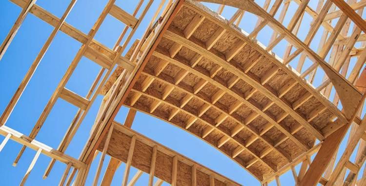 New construction home framing against blue sky.