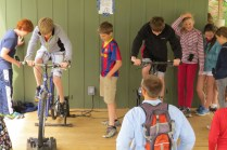 Ecology school students learn that water doesn't magically appear from the tap as they pedal bikes to generate enough electricity to pump water to the bunkhouse sinks and showers.