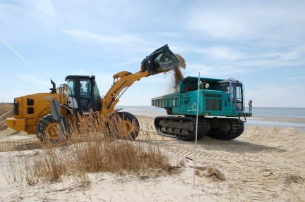 Work at one of the restored beaches, Kimbles Beach. A wheel loader fills the rubber-tracked dump truck. Credit: Eric Schrading/U.S. Fish and Wildlife Service