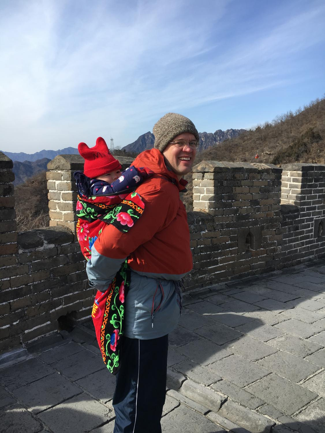Vince Tweddell, an adjunct journalism and English instructor, carries his daughter at the Great Wall of China.