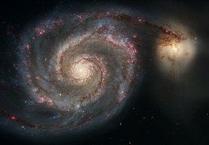 Majesteettinen kierregalaksi M51, jota on nimitetty 'pyörteeksi'. Ohi kulkevan galaksin vetovoima aiheuttaa vääristymiä galaksin kierteisiin. Kuva: ESA Hubble
