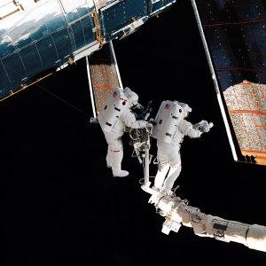 Astronautit korjaavat aurinkopaneeleja. Kuva: ESA Hubble.