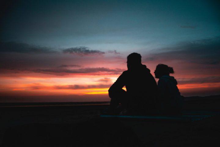 夕日をバックに語り合うカップル