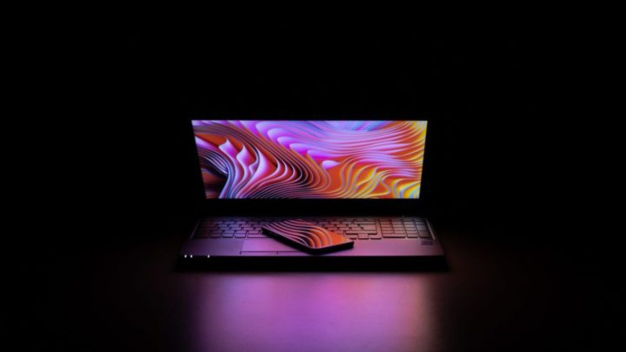 暗い部屋にカラフルな画面のパソコン