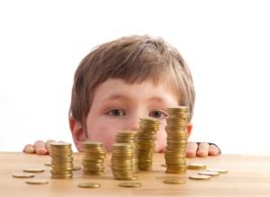 Junge schaut sich Geldtürme an, die auf einem Tisch liegen