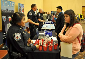 Tyler Police Officer Bianca Cortez, left, chats with junior criminal justice major Brittnany Martinez about her experience working as a midnight patrol officer in East Texas. The Department of Criminology & Criminal Justice Career Fair was held April 16 and sponsored by the Alpha Phi Sigma Honor Society. (Photo by James Dunning)
