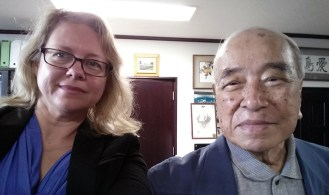 Communication graduate student and broadcast lecturer LaDonna Aiken, left, poses with former Okinawa governor Masahide Ota during her research trip to Japan earlier this year. (Photo contributed)