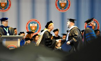 Associate Dean Elisabeth Cawthon congratulates a graduate Friday, May 15, during the College of Liberal Arts' Spring 2015 Commencement at College Park Center. (Photo by James Dunning/COLA Communications)