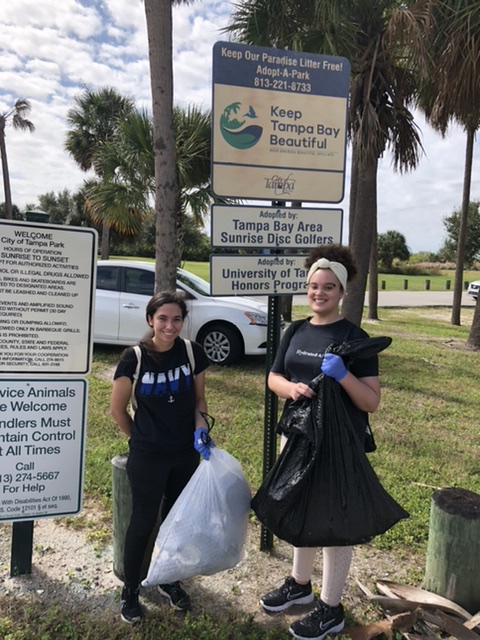 two young women in front of a Keep Tampa Bay Beautiful sign