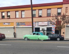 The prettiest teal car driving in front of the offices