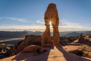 Rising sun peeking through a stone arch