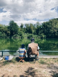 Adult and child fishing on a river bank.
