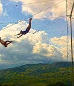 Trapeze artists in mid-transfer.