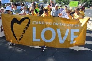 "UU community marches with sign ""Standing on the Side of Love"""
