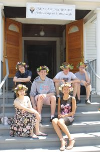 Picture of bridging students sitting in front of fellowship with flower crowns on their heads.